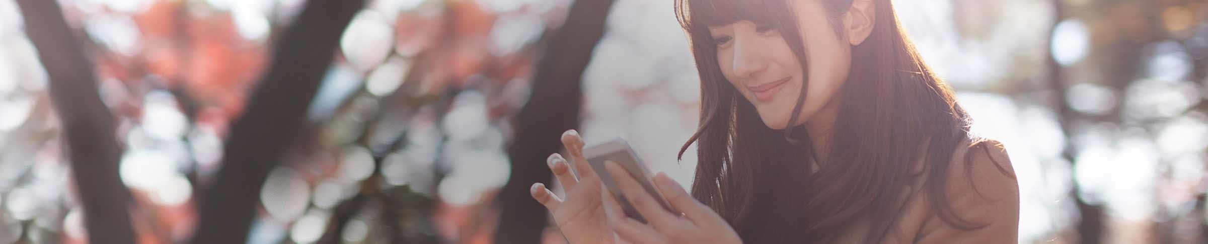 En ung kvinna utomhus som tittar på sin telefon