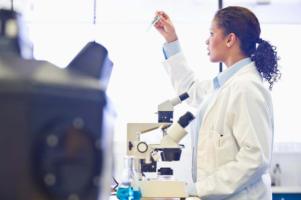 Doktor som ser in i ett mikroskop i ett labb.