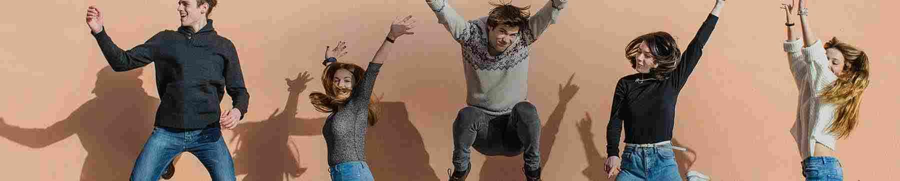 En grupp vänner som hoppar med armarna i luften medan de skrattar och ler
