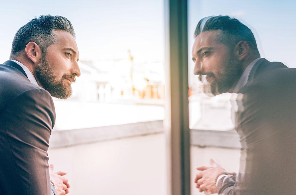 Bild av en mogen man som tittar på sin egen spegelbild i ett fönster