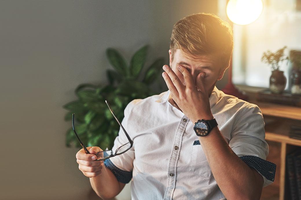 Bild av en man som tar av sina glasögon för att gnugga sina ögon