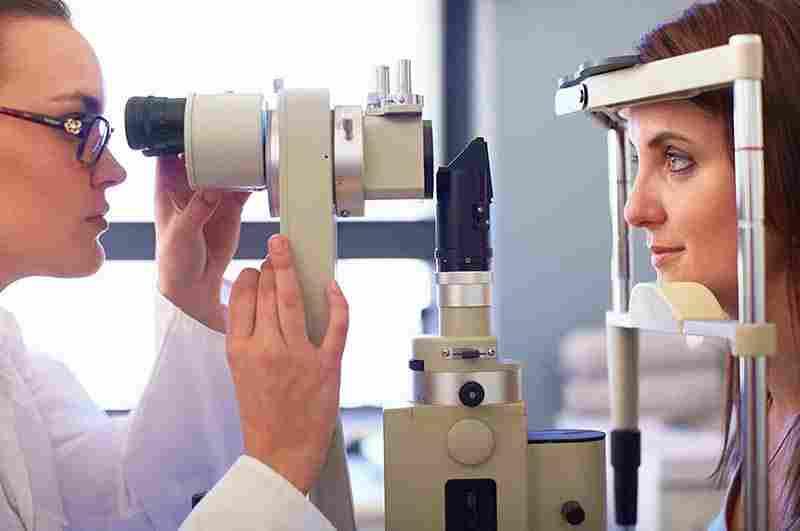 En sidobild av en optiker och en ung kvinna som tittar i en retinakamera