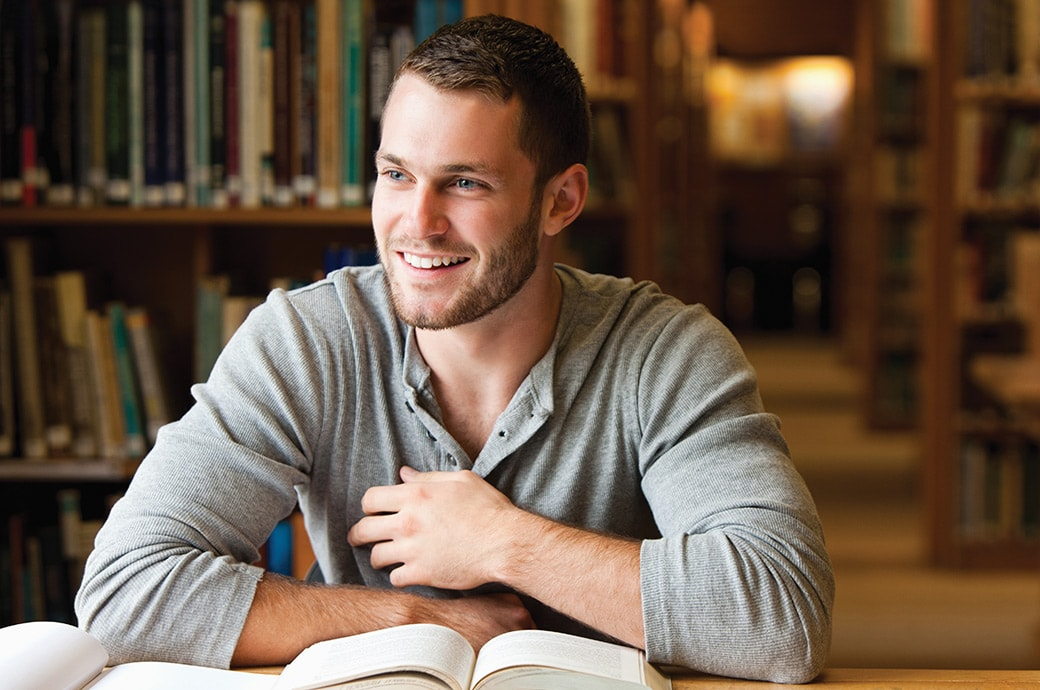 A man at the library smiling with books on the table