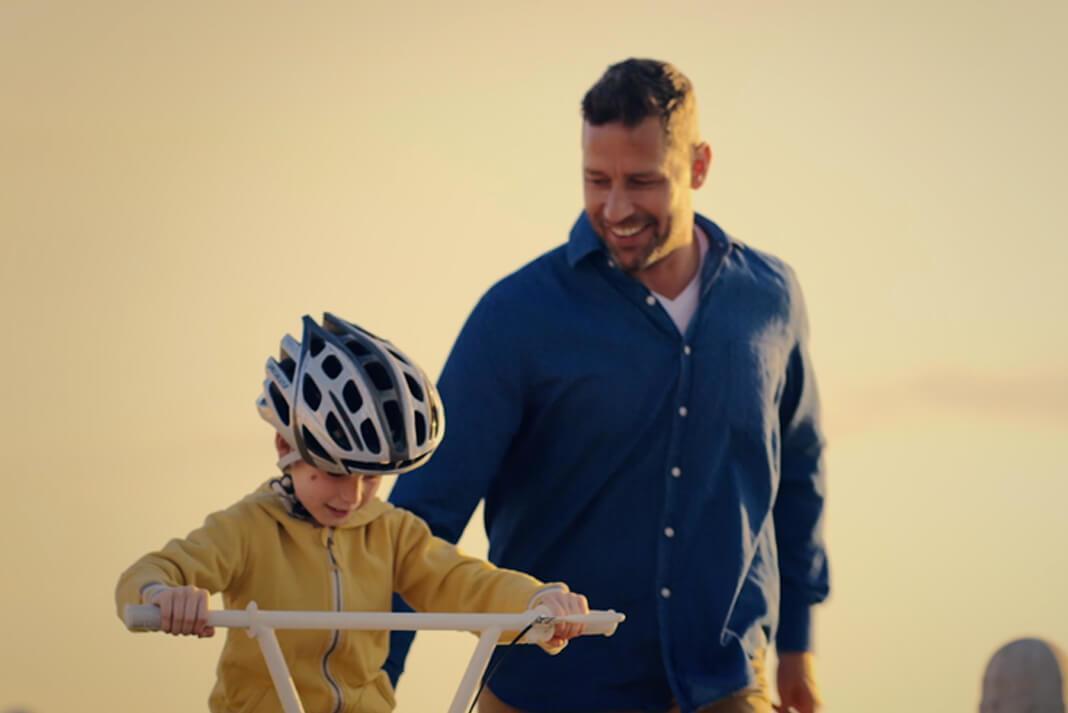 En bild av en liten pojke som lär sig att cykla med hjälp av sin far