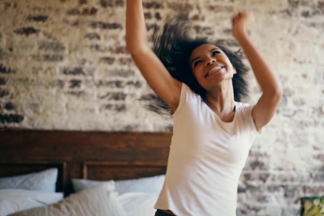 En bild av en ung kvinna som dansar i sitt sovrum