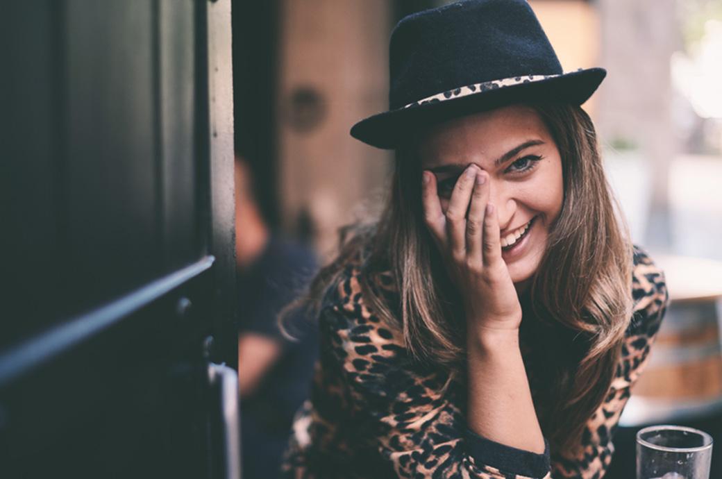 Bild av en kvinna utomhus som håller sig för ögat