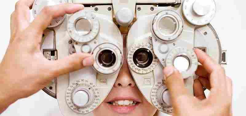 En optiker som granskar en foropter