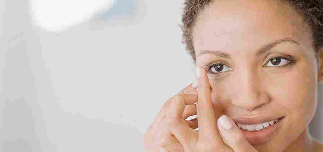 n kvinna som har en kontaktlins på sitt finger och håller på att sätta in den i ögat